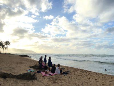 thanksgivindayのノースショア。家族みんなで浜辺で子どものサーフィン見てるfamily.